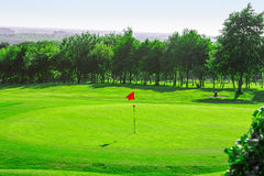 Golf course. Red golf flag on the golf course Stock Photo