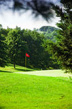 Golf course with red flag in the middle Royalty Free Stock Images