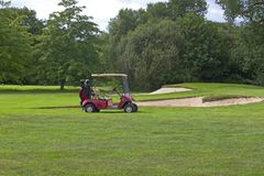 Golf green with red golf cart. A golf course with a red golf cart and trees in England stock photos