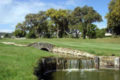 Golf course, river and bridge at San Roque in Spain. Golf course, fairway, river or stream and bridge on a sunny day at San Rogue golf in Spain on the Costa del Stock Photo