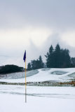 Golf course on a snowy winter morning. A golf course in Scotland on a snowy winter morning in December. View from a green with a blue flag, with trees, mist and Royalty Free Stock Photography