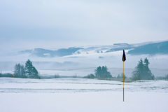 Golf course on a snowy winter morning. A golf course in Scotland on a snowy winter morning in December. View from a green with a blue flag, with trees, mist and stock photography