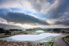 Golf course on a snowy winter morning. View from the tee of a golf course in Scotland on a snowy winter morning, with dramatic cloudy sky overhead Stock Image