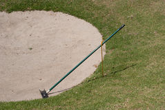 Golf course trap. Golf course sand trap with rake Royalty Free Stock Image