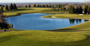 Golf course vista. Beautiful scenic view of a golf course, including tee, water, green and sand traps Royalty Free Stock Images