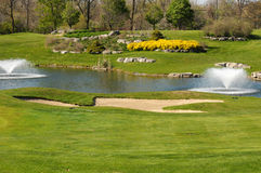 Golf course with water fountains Stock Images