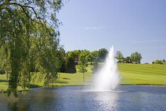 Golf Course Water Source. A reflective pond is the water source for this Wisconsin Golf Course. The fountain adds beauty and the clubhouse is up at the top of Royalty Free Stock Image