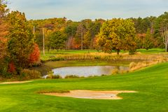 Golf course water trap. A golf course water trap and fairways amid autumn colors Stock Photos