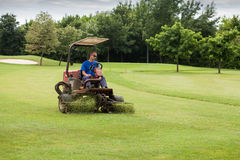 Golf course worker mows the grass