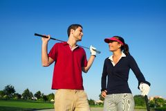 Golf course young happy couple players. Golf course young happy players couple talking posing on bunker Stock Image