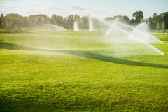 Golf courses watered special devices. Green golf courses watered special devices Stock Photos