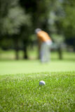 Golf couse detail. Golf course with the ball in front and blurred people in the back Royalty Free Stock Image