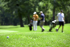 Golf couse detail. Golf course with the ball in front and blurred people in the back Royalty Free Stock Photos