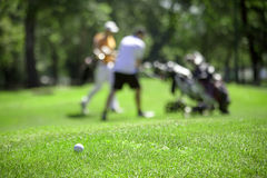 Golf couse detail. Golf course with the ball in front and blurred people in the back Royalty Free Stock Photo