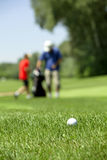 Golf couse detail. Golf course with the ball in front and blurred people in the back Stock Photography