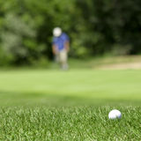 Golf couse detail. Golf course with the ball in front and blurred people in the back Stock Images
