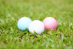 Golf crystal white, pink, and blue ball on green grass in golf course Stock Photos