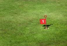 Golf Cup Marker. Old tin golf number one cup marker flag on a crazy golf green Stock Image