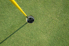 Golf cup with yellow pole Royalty Free Stock Image