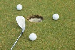 golf de 3 blancos al lado del agujero Imagenes de archivo