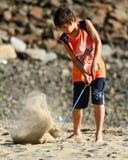 Golf de la práctica del niño en la playa Fotos de archivo libres de regalías