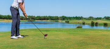 Golf del gioco dell'uomo Con il bastone sul campo verde Immagine Stock