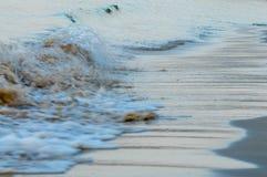 Golf die bij kust over bruin strandzand rollen Royalty-vrije Stock Foto's