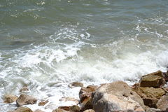 Golf die op zandig en rotsachtig strand verpletteren Stock Fotografie