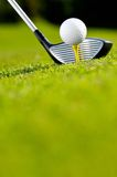 Golf driver and ball on tee. Close up of golf driver or wood club and white ball on tee on green course Royalty Free Stock Photos