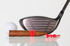 Golf driver and different cigars on a glass desk Stock Photos