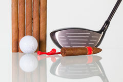 Golf driver and different cigars on a glass desk Royalty Free Stock Image