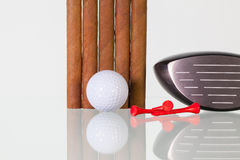 Golf driver and different cigars on a glass desk Stock Photo