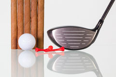 Golf driver and different cigars on a glass desk Stock Images