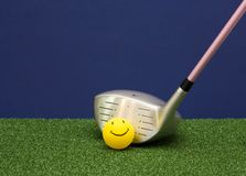 Golf Driver And Happy Face Ball. Happy Face Golf ball and driver on a blue and green background. Ladies pink shaft. Lots of copy space Royalty Free Stock Image