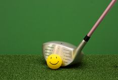 Golf Driver And Happy Face Ball. Golf happy face ball and driver on a green and grass background. Ladies pink shaft. Lots of copy space Royalty Free Stock Image