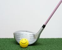 Golf Driver With Happy Face Ball. Golf driver with a happy face ball on green foreground and gray background. Room for copy Royalty Free Stock Images