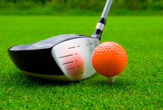 Golf driver with orange ball. Stock Image