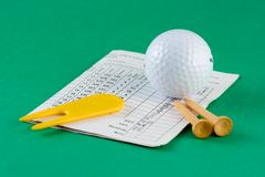 Golf Equipment. Golf ball, tees, divot repairer and scorecard Stock Photos