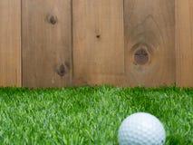 Golf et boule sur le fond d'herbe verte et en bois Photo stock