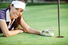 Golf feliz de la mujer que empuja la pelota de golf en el agujero Imágenes de archivo libres de regalías