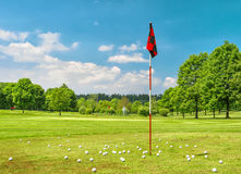 Golf field and cloudy blue sky. Spring landscape with grass and Royalty Free Stock Photography
