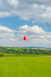 Golf field green grass red flag cloudy blue sky Royalty Free Stock Image