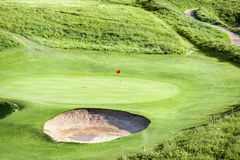 Golf field with hole and flag Stock Photos