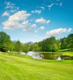 Golf field. Landscape with green grass and beautiful blue sky Royalty Free Stock Image