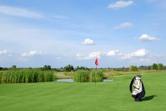 Golf field with red flag and bag Royalty Free Stock Image