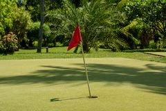 Golf field with red flag at the tropical island at Maldives. Golf field with red flag located at the beautiful tropical island at Maldives Royalty Free Stock Photography