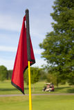 Golf Flag. A close up shot of a red golf flag with a golf cart in the background out of focus royalty free stock photography
