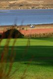 Golf flag. Late afternoon shadows fall on golf green Royalty Free Stock Photos