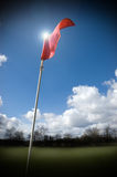 Golf Flag. Red golf flag fluttering in the wind lit by the sun royalty free stock photos