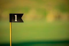 Golf Flag for First Hole. Flag for first hole with blurred putting green in background Stock Photography